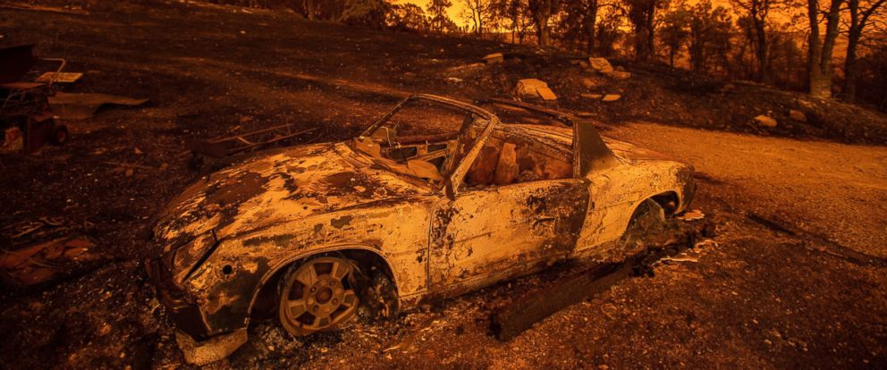 Cars scorched by the Carr Fire rest at a residence in Redding, Calif., on Friday, July 27, 2018. The fire rapidly expanded Thursday when flames swept through the Gold Rush town of Shasta, then jumped the Sacramento River into Redding.