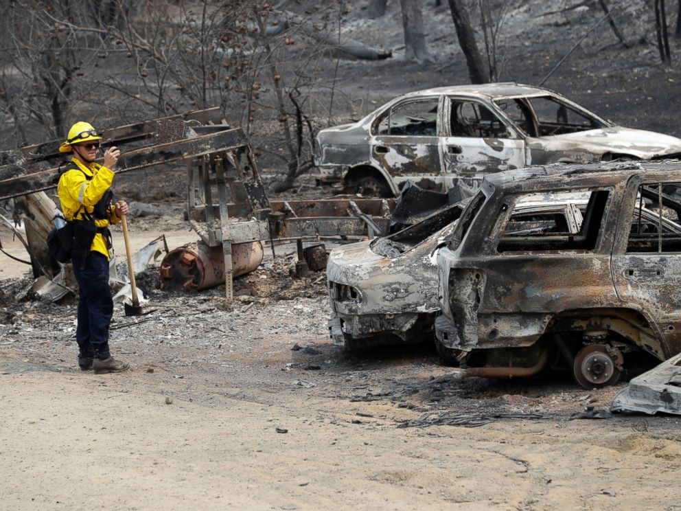 San Bernardino County Fire Department firefighter James Lippen takes photos of the damage caused by a wildfire, Sunday, July 29, 2018, in Keswick, Calif.