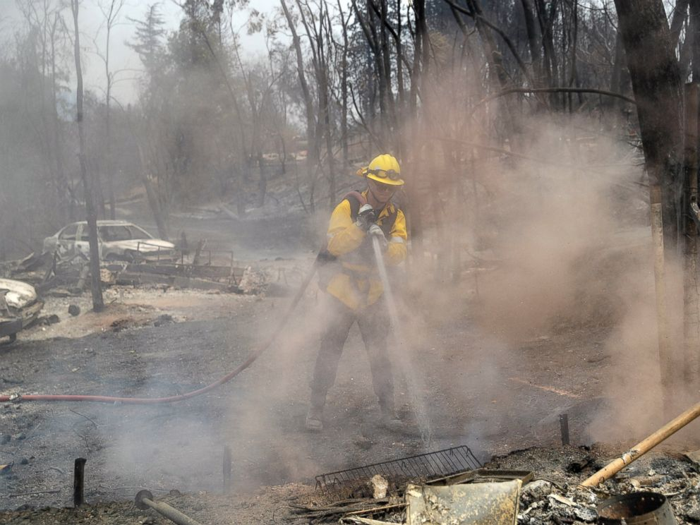 San Bernardino County Fire Department firefighter James Lippen hoses down hot spots left behind by a wildfire, Sunday, July 29, 2018, in Keswick, Calif.