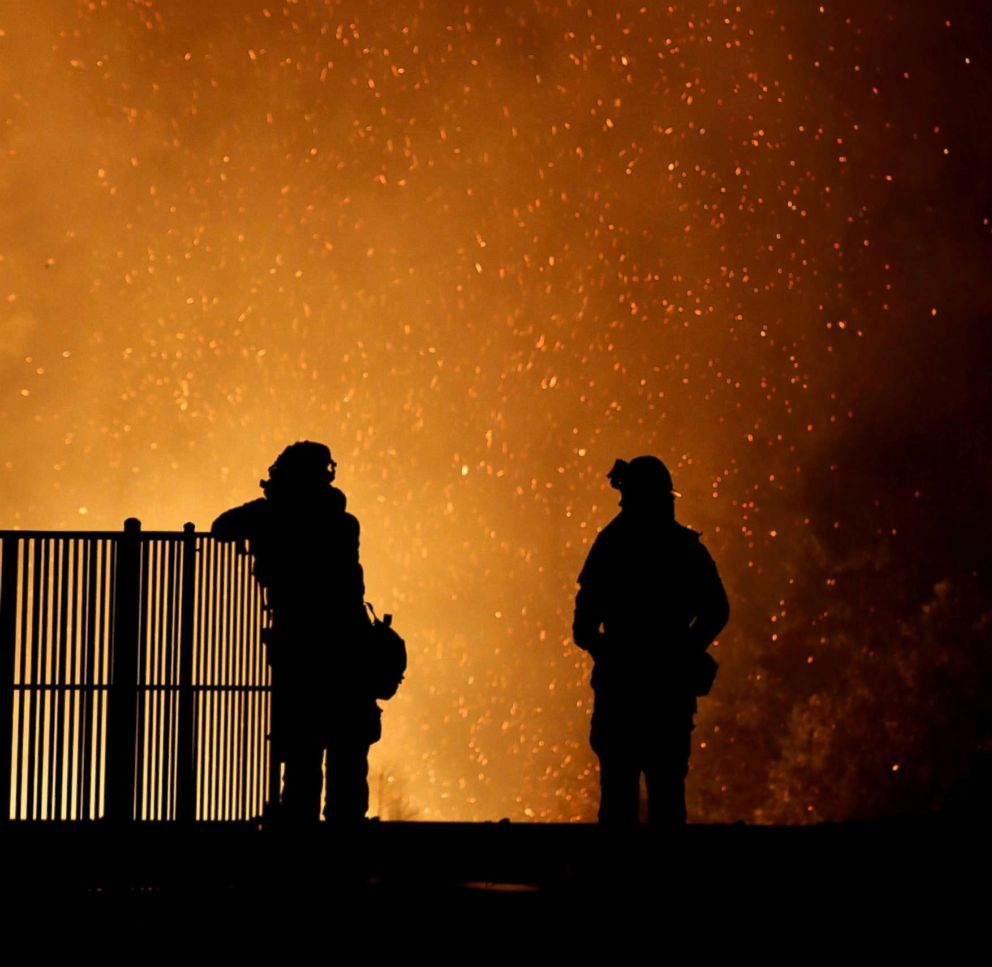 PHOTO: Burning embers swirl around firefighters as they stand guard at a home while battling the Carr Fire, west of Redding, Calif., July 27, 2018.