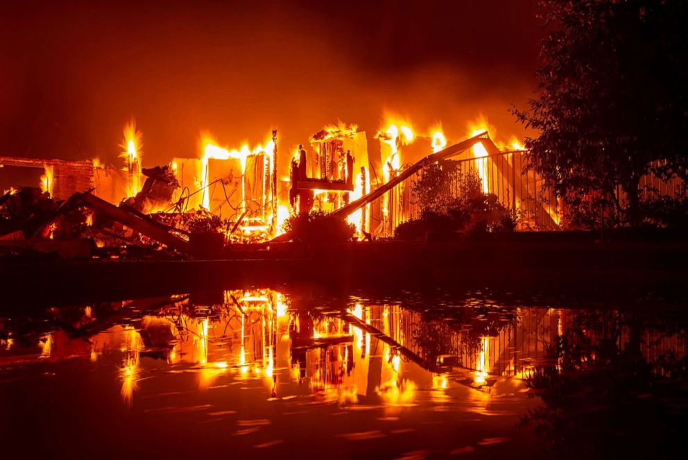 PHOTO: A burning home is reflected in a pool during the Carr fire in Redding, Calif., July 27, 2018.