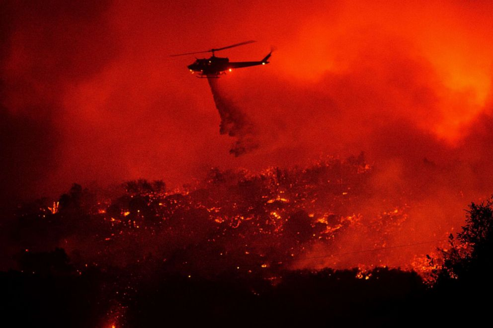 PHOTO: A helicopter drops water on the Cave Fire burning along Highway 154 in Los Padres National Forest, Calif., above Santa Barbara, Nov. 26, 2019.