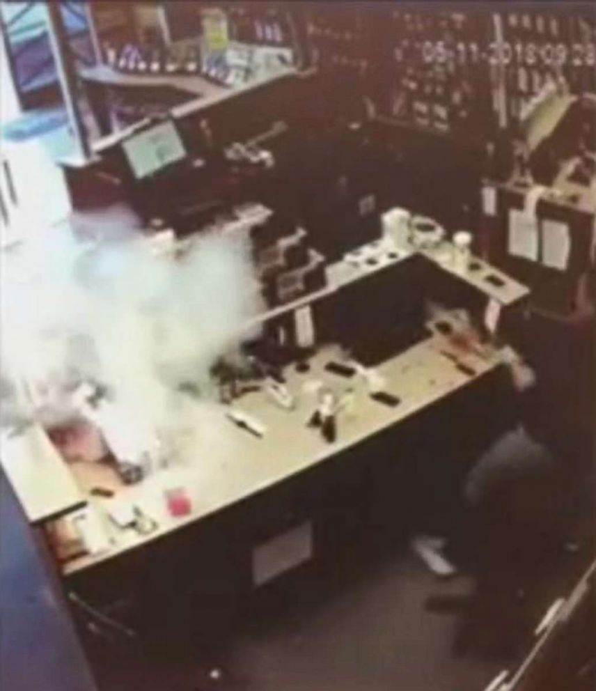 PHOTO: A frame taken from a video showing an iPhone that burst into flames, at left, just a few feet away from an employee at a store.