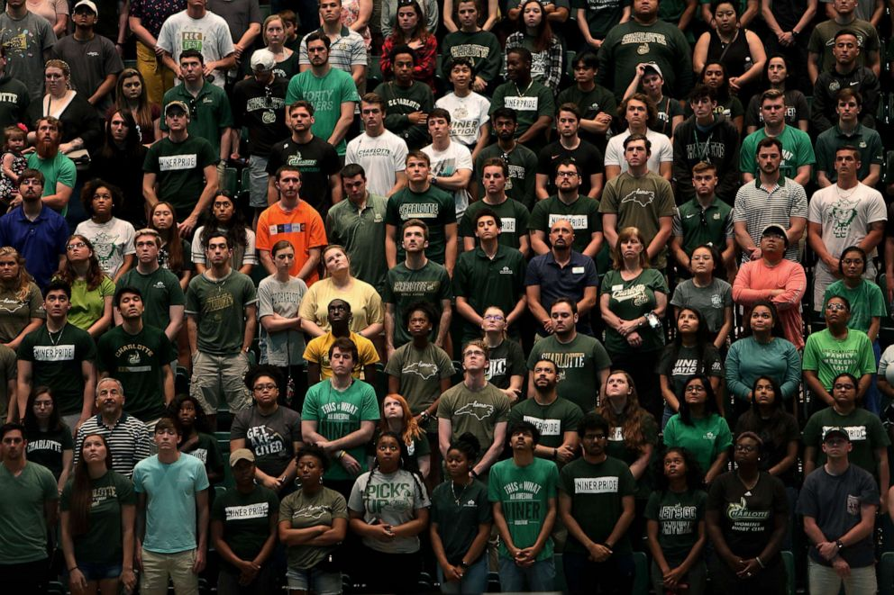 PHOTO: People stand during a vigil in the Dale F. Halton Arena at University of North Carolina at Charlotte campus the day after a gunman opened fire on students, May 1, 2019.