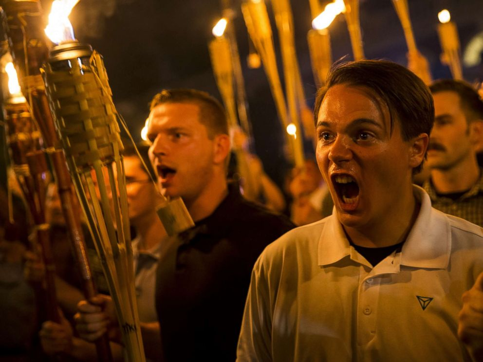 PHOTO: Peter Cvjetanovic, right,along with Neo Nazis, Alt-Right, and White Supremacists encircle and chant at counter protesters after marching through the University of Virginia campus with torches in Charlottesville, Va., on Aug. 11, 2017.