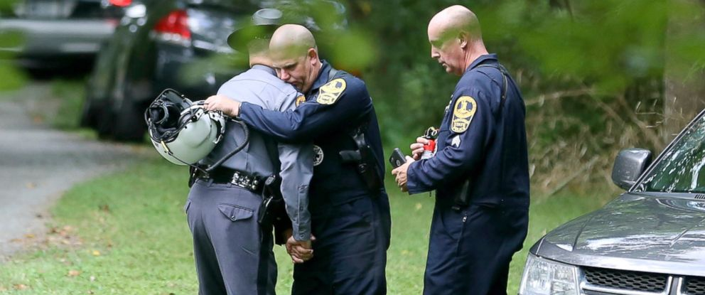 PHOTO: Authorities embrace while working near the scene of a deadly helicopter crash near Charlottesville, Va., Aug. 12, 2017.