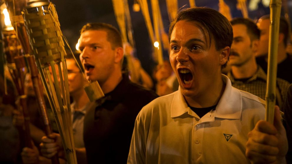 Peter Cvjetanovic, right, along with Neo Nazis, Alt-Right, and White Supremacists encircle and chant at counter-protesters after marching through the University of Virginia campus with torches in Charlottesville, Va., Aug. 11, 2017.