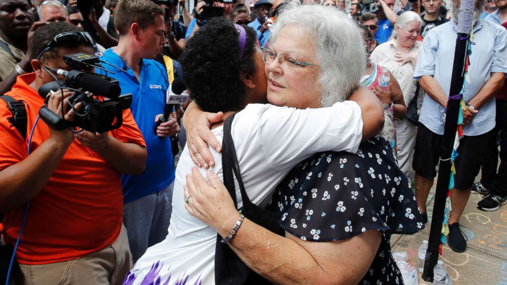 """Susan Bro, the mother of Heather Heyer who was killed during last year's """"Unite the Right"""" rally, embraces supporters after laying flowers at the spot her daughter was killed in Charlottesville, Va., Aug. 12, 2018. Bro said there's still """"so much healing to do."""" She said the city and the country have a """"huge racial problem"""" and that if it's not fixed, """"we'll be right back here in no time."""""""
