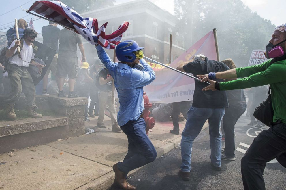 A white supremacist tries to strike a counter protester with a flagpole during clashes at Emancipation Park in Charlottesville, Va., Aug. 12, 2017.