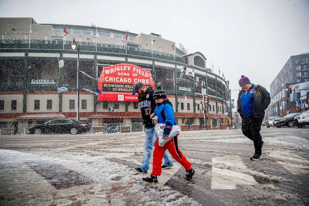 PHOTO: Pedestrians walk through the snow near Wrigley Field after the Cubs game was canceled due to weather Sunday April 14, 2019, in Chicago.