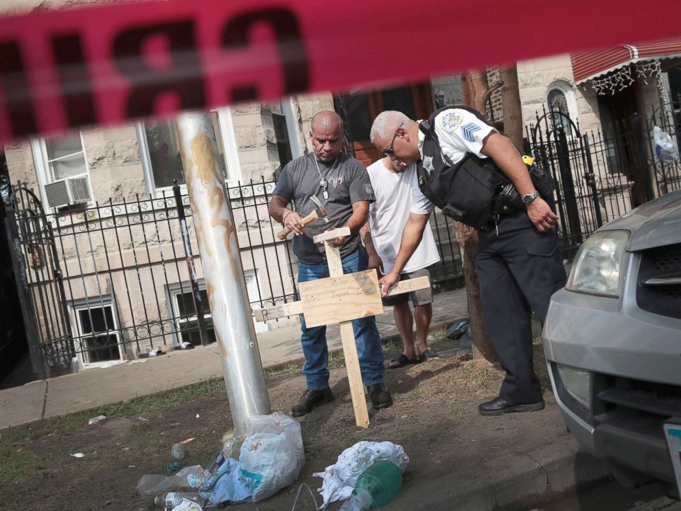 PHOTO: A police officer helps as Omar Acevedo pounds a cross bearing the names of victims into the dirt outside a home where eight people perished, including six children, Aug. 26, 2018, in Chicago.