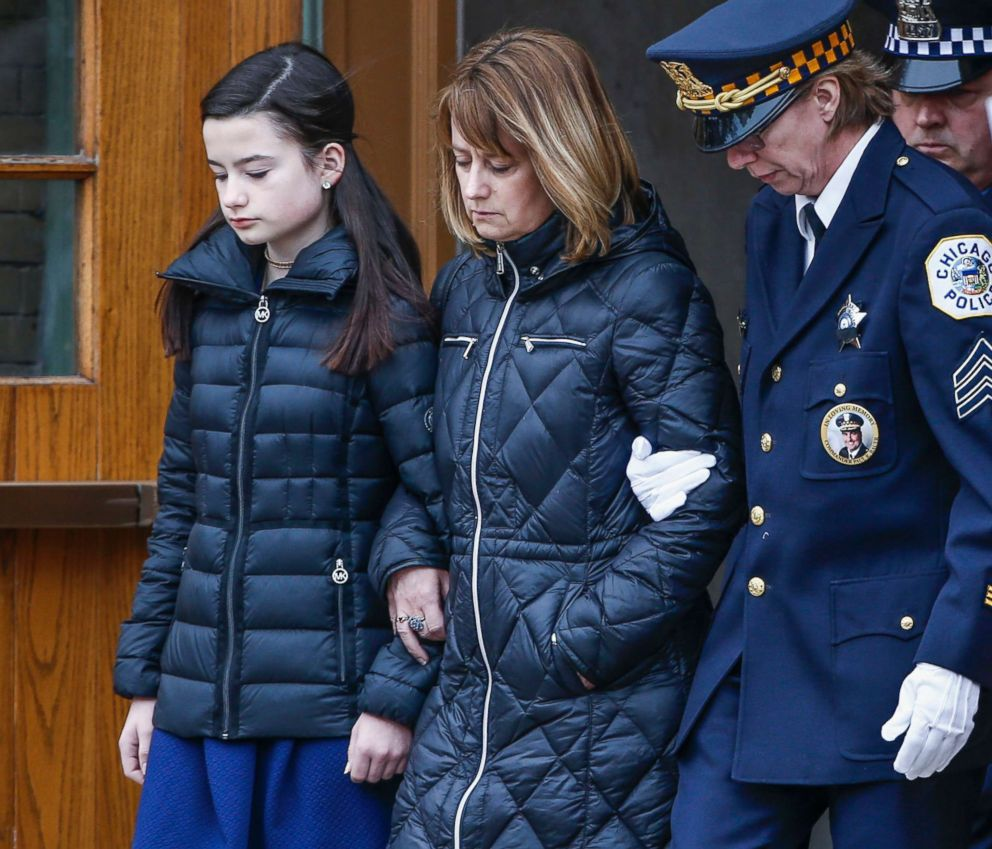 PHOTO: Grace Bauer, left, and her mother Erin, center, are escorted out of the church after attending the funeral service for their father and husband Chicago Police Commander Paul Bauer in Chicago, Feb. 17, 2018.