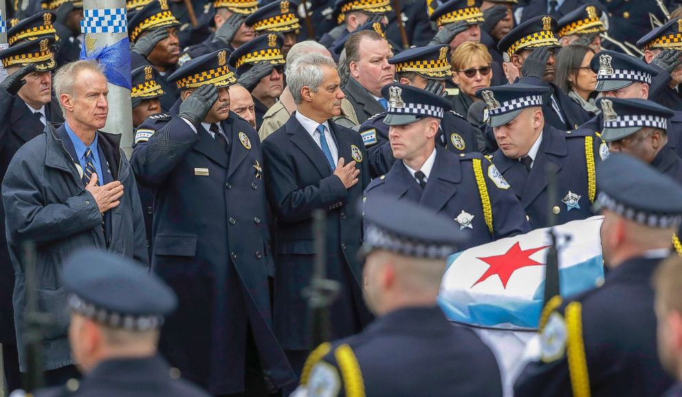 PHOTO: Illinois Gov. Burce Rauner, left, Chicago Police Superintendent Eddie Johnson, second from left, and Mayor Rahm Emanuel salute the casket of Cmdr. Paul Bauer after a funeral mass, Feb. 17, 2018, in Chicago.