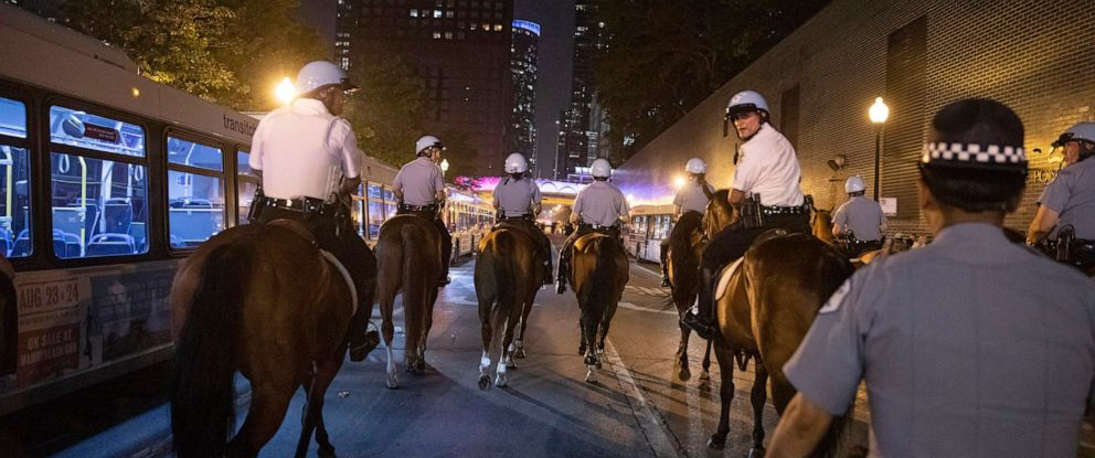 PHOTO: Chicago Police Department officers guard people as they stream out of Chicagos Navy Pier after reports of stabbings and threatening injuries after the 4th of July celebrations, July 4, 2019.