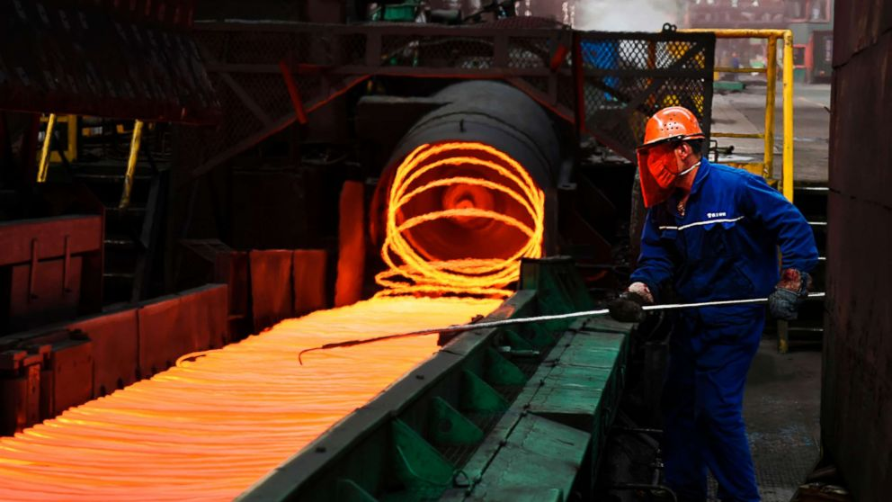 An employee sorts hot red steel at a steel plant in Zouping in China's eastern Shandong province on March 5, 2018.