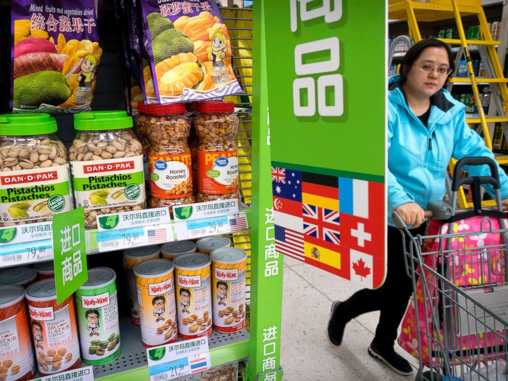 PHOTO: A woman pushes a shopping cart past a display of nuts imported from the United States at a supermarket in Beijing, March 23, 2018.