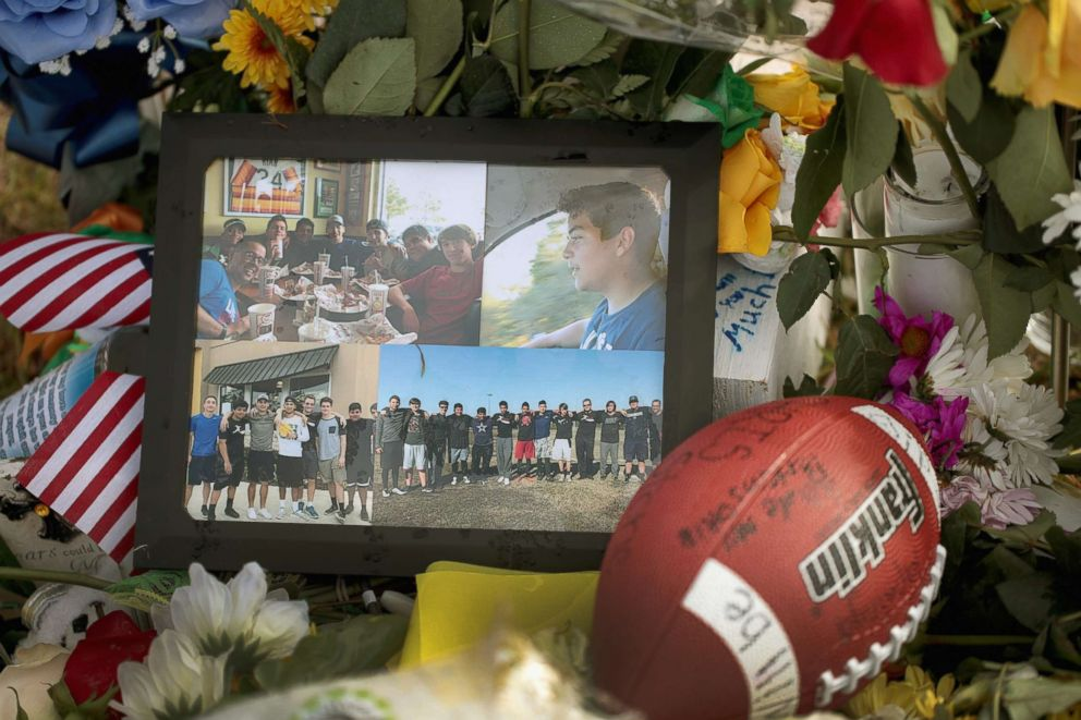 PHOTO: Photos, a football and flowers sit in front of a cross bearing the name of Chris Stone at a memorial in front of Santa Fe High School, May 22, 2018 in Santa Fe, Texas.
