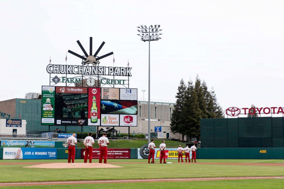 PHOTO: The Fresno Grizzlies stand in the field during the National Anthem before a game against the Reno Aces at Chukchansi Park, April 8, 2019, in Fresno, California.