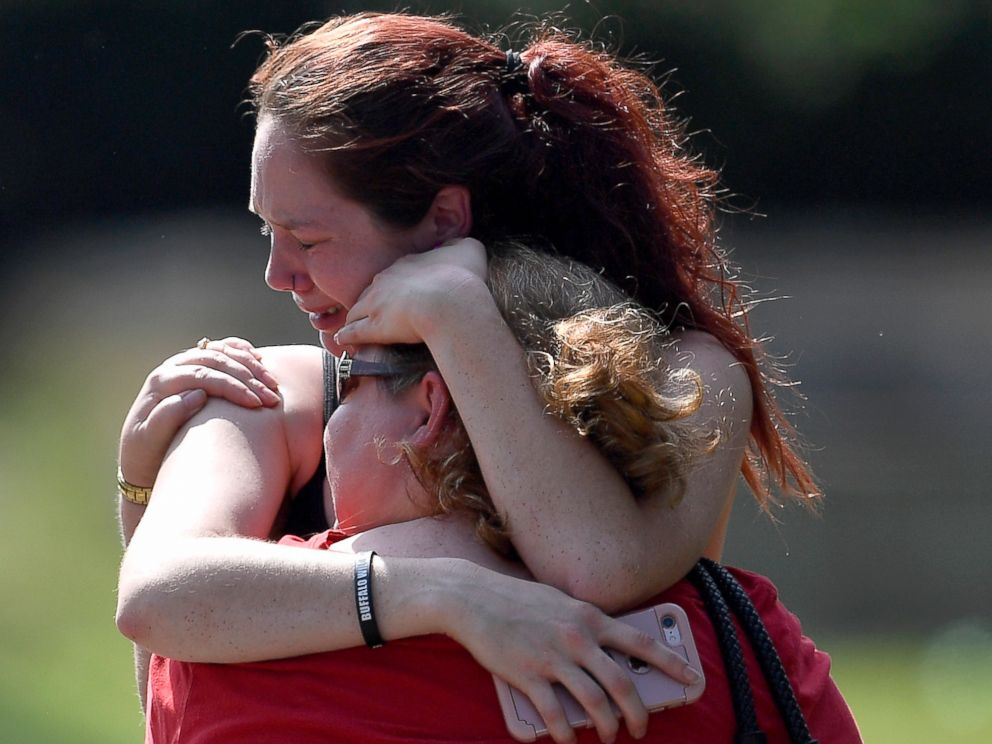 PHOTO: Kaitlyn Adams, a member of the Burnette Chapel Church of Christ, hugs another church member at the scene after a deadly shooting at the church, Sept. 24, 2017, in Antioch, Tenn.