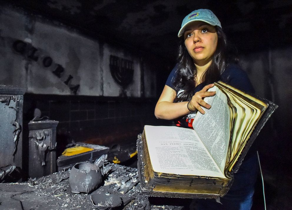PHOTO: Tasha Collazo, a granddaughter of Pastor Carmen L. Cruz, shows a bible that survived the fire at Iglesia Pentecostal De Bethlehem Church on April 23, 2019 in Allentown, Pa.