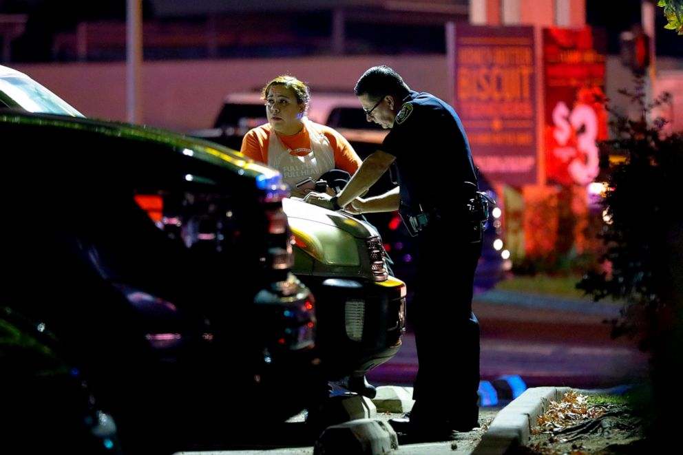 PHOTO: A San Diego Police officer question witnesses just outside a Churchs Chicken eatery after a shooting that left one dead and two injured, Oct. 6, 2019.