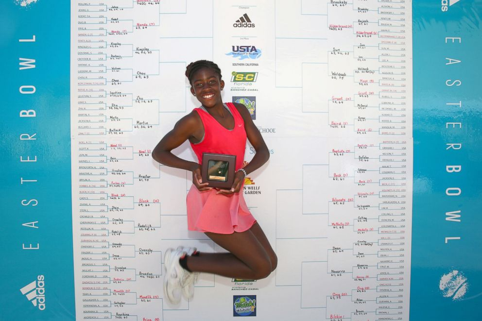 PHOTO: Clervie Ngounoue presents a photograph in March 2018 after winning the 51st Annual Adidas Easter Bowl - the USTA National Spring Championship.