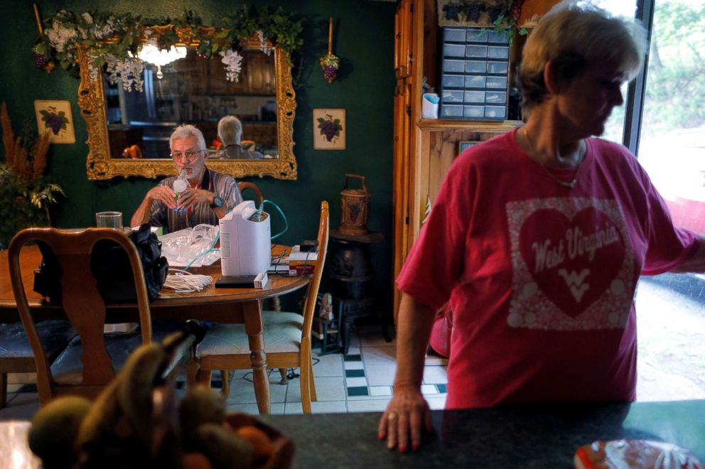 Retired coal miner Kennith Adams, who has complicated black lung disease and lives connected to an oxygen supply 24-hours a day, inhales medicine while his wife Tammie keeps him company, at their home in Princeton, W.Va., May 17, 2018. Adams has re-applied after his first federal black lung disability application was denied despite his medical condition and the coal company he worked for claimed he never worked there.
