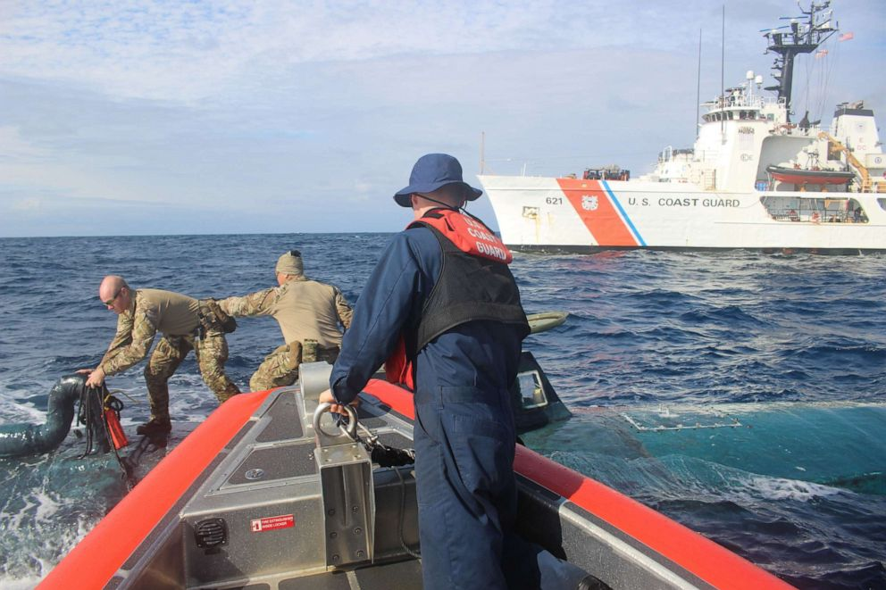 PHOTO: Members of a U.S. Coast Guard Cutter Valiant boarding team transfer narcotics between an interceptor boat and a suspected smuggling vessel in the Eastern Pacific in September 2019.