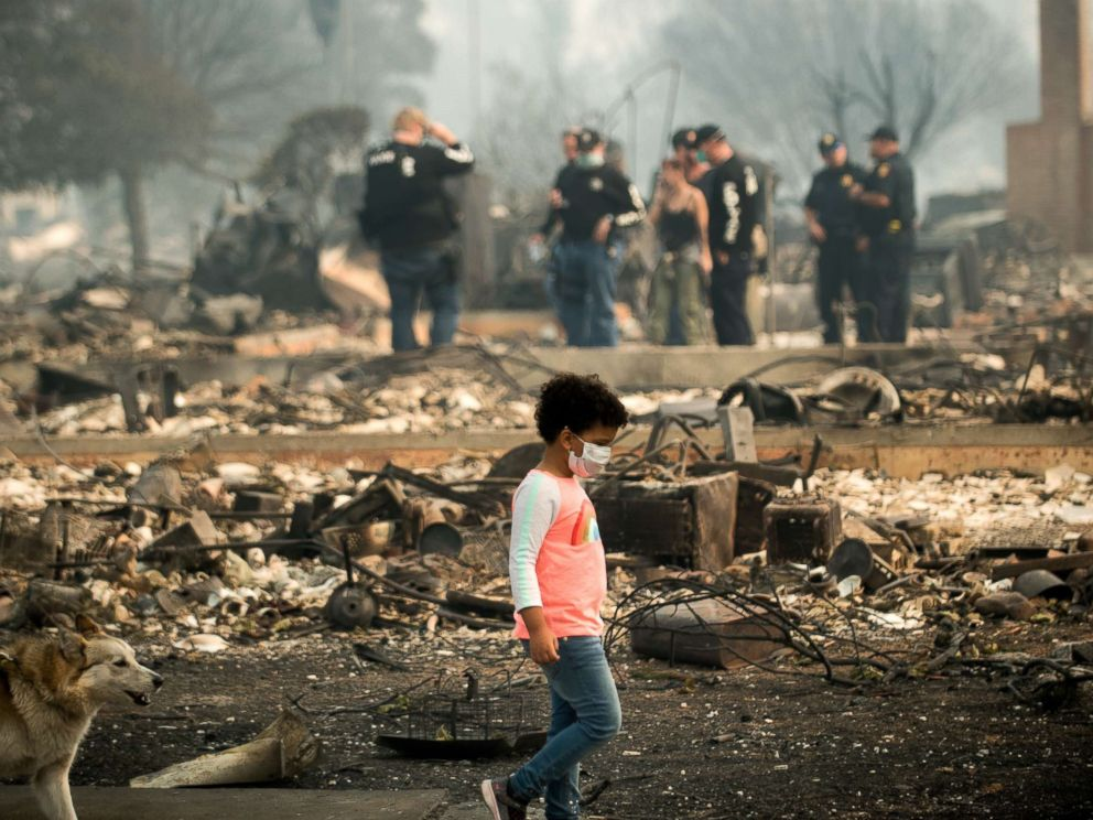 PHOTO: A child walks by as police officers search for signs of a Coffey Park resident who was missing since the Tubbs fire roared through the neighborhood, Oct. 10, 2017 in Santa Rosa, Calif.