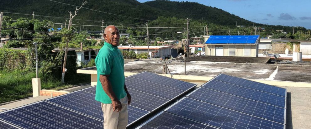 Community leader Angel Colon with the solar panels atop a building in Daguao, Puerto Rico.