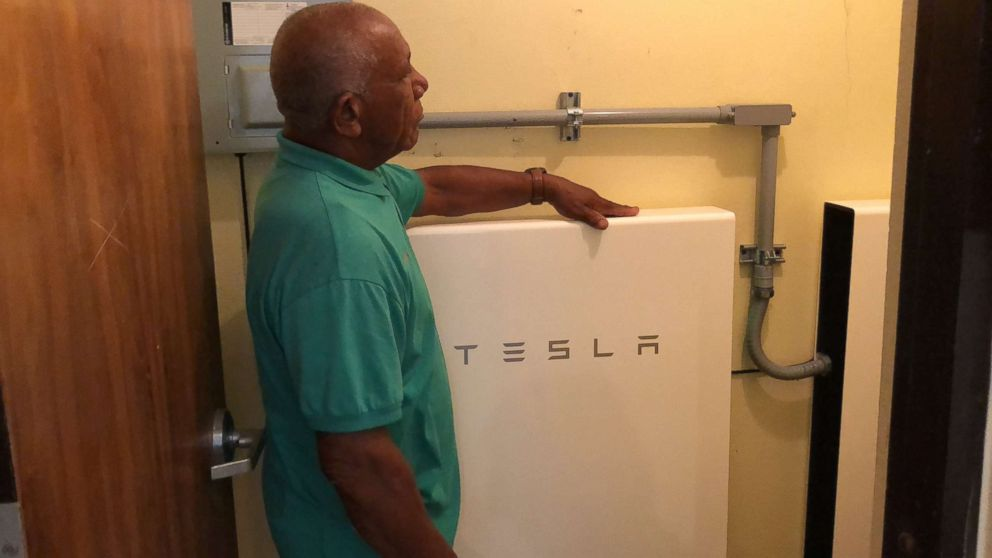 Community leader Angel Colon next to a TESLA Powerwall battery, which stores solar energy.