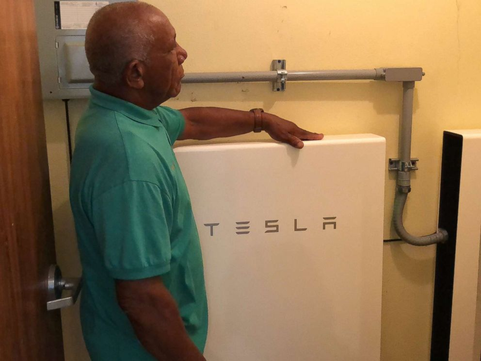 Community leader Angel Colon next to a TESLA Powerwall battery, which stores solar energy. how being prepared for hurricane season starts with solar power in one puerto rico town How being prepared for hurricane season starts with solar power in one Puerto Rico town colon tesla pr mo 20180530 hpMain 4x3 992