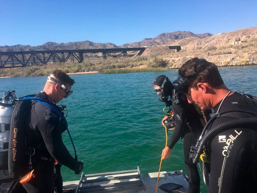 In this photo released by Los Angeles Sheriff Department Special Enforcement Bureau their dive team assists San Bernardino County Sheriffs in the search for three missing persons in the Colorado river Monday, Sept. 3, 2018, near Topock, Ariz.