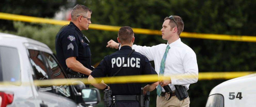 PHOTO: Law enforcement officials investigate around the scene of a shooting in a parking lot behind a dentists office, June 14, 2018, in Westminster, Colo.
