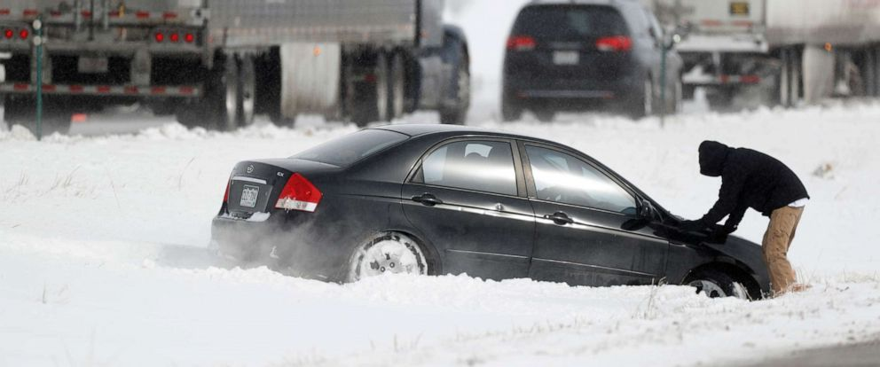 PHOTO: A motorist struggles to free his sedan after sliding off Interstate 70, which was later closed by officials, in Aurora, Colo., Tuesday, Oct. 29, 2019, as an autumn storm sweeps over the Intermountain West.