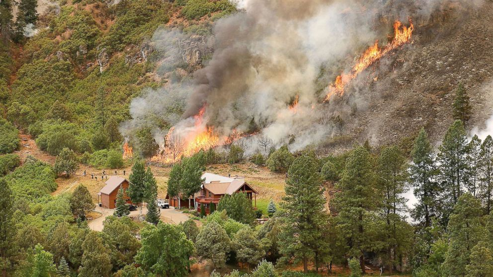 Firefighters monitor flames behind a home during a burnout operation that was performed south of County Road 202 near Durango, Colo., June 11, 2018. The burnout  is used to take away fuel from wildfires. Firefighters use the technique to burn in conditions so that they can control the fire and prevent the loss of homes.