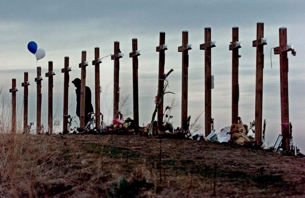 PHOTO: On April 28, 1999, a woman looks at crosses posted on a hill above Columbine High School in Littleton, Colo., in remembrance of the people who died during a shooting rampage at the school.