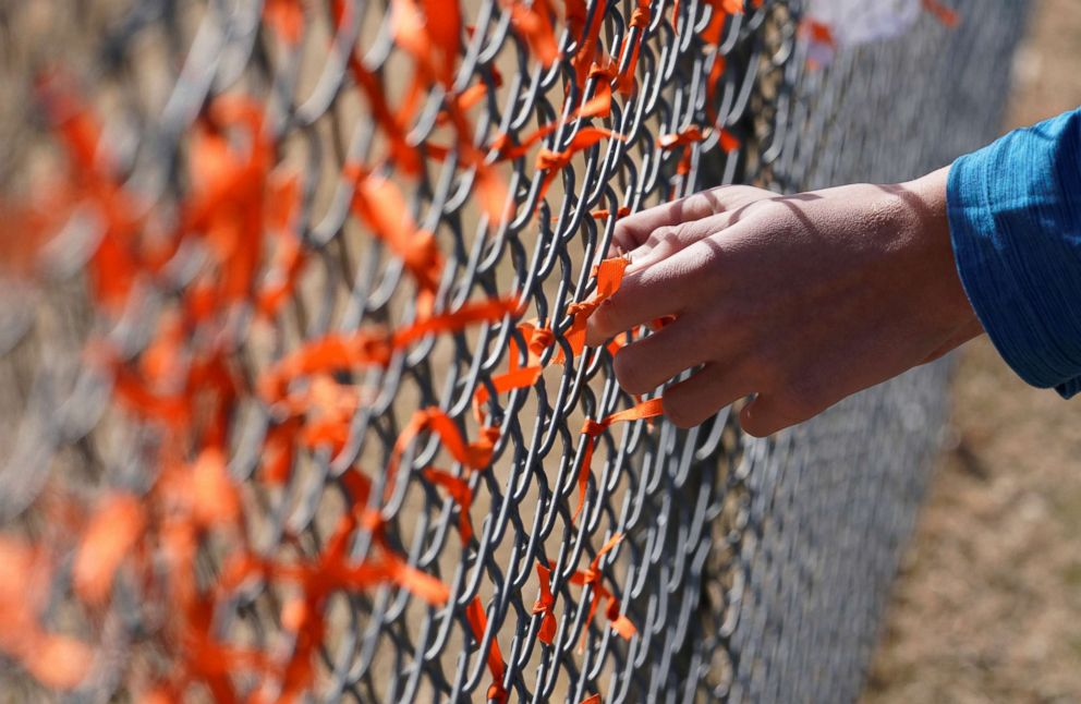 PHOTO: Columbine High School student Andrew Pavicich ties a commemorative ribbon on the fence in front of the school during a national school walkout in honor of 17 students and staff killed at Marjory Stoneman's Douglas High School, March 14, 2018.