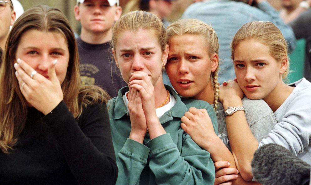 PHOTO: Students from Columbine High School in Littleton, Colo., watch as the last of their fellow students are evacuated from the school building following a mass shooting at the school on April 20, 1999.