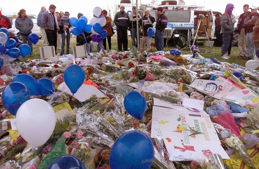 PHOTO: Residents of Littleton, CO stand near a carpet of flowers, mourning the dead at Columbine High School, April 21, 1999. Thirteen fellow students were killed and twenty more were injured in a shooting at the school.