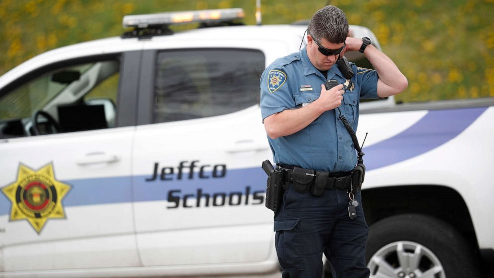 An officer from Jefferson County, Colo., Schools listens on his radio as students leave Columbine High School, April 16, 2019, in Littleton, Colo.