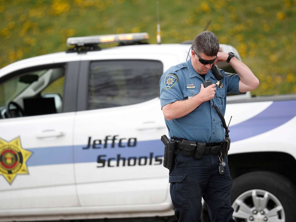 PHOTO: An officer from Jefferson County, Colo., Schools listens on his radio as students leave Columbine High School, April 16, 2019, in Littleton, Colo.