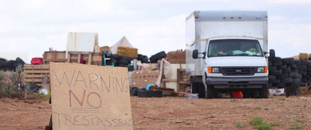 """PHOTO: A """"no trespassing"""" sign outside of the location where people camped near Amalia, N.M., Aug. 5, 2018."""