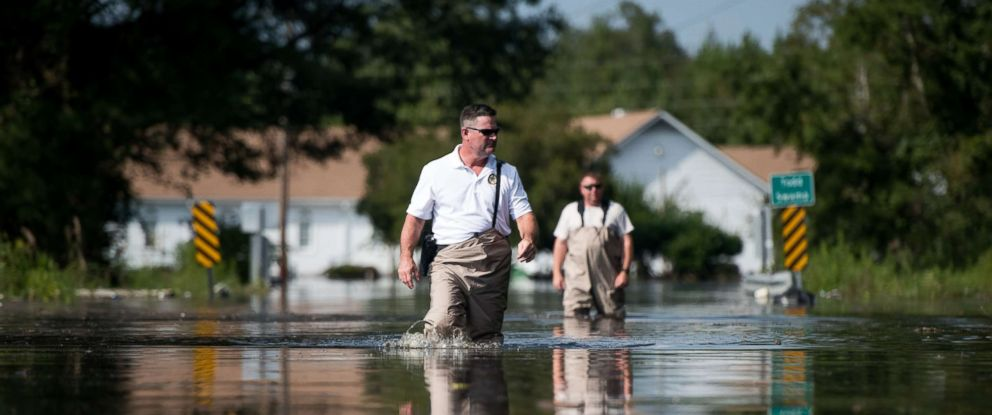 PHOTO: A Department of Natural Resources officer, left, and a South Carolina Law Enforcement agent walk through floodwaters caused by Hurricane Florence near the Todd Swamp, Sept. 21, 2018, in Longs, South Carolina.