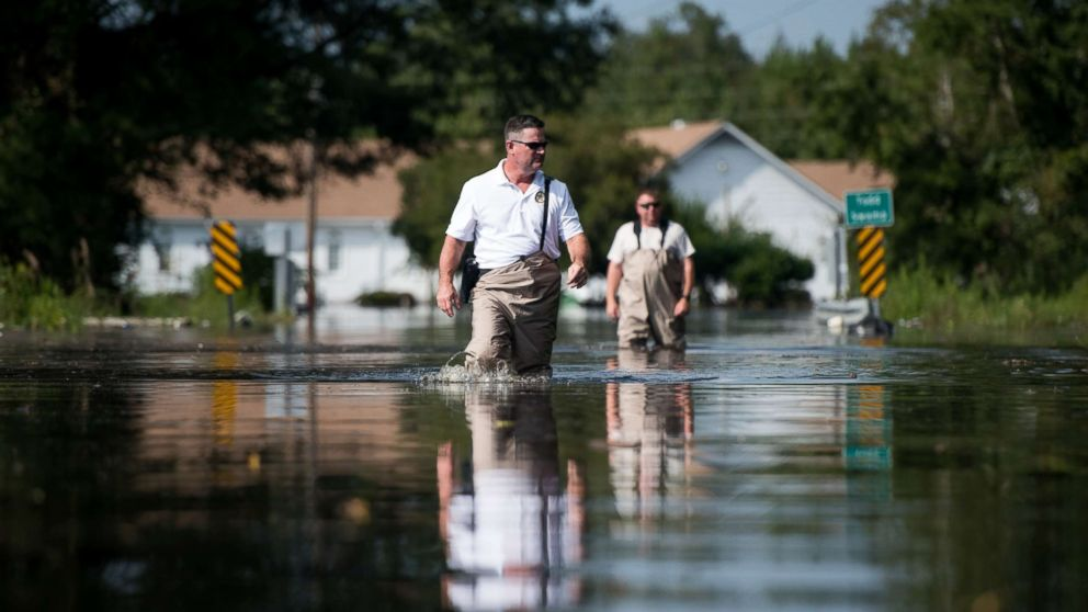 A Department of Natural Resources officer, left, and a South Carolina Law Enforcement agent walk through floodwaters caused by Hurricane Florence near the Todd Swamp, Sept. 21, 2018, in Longs, South Carolina.