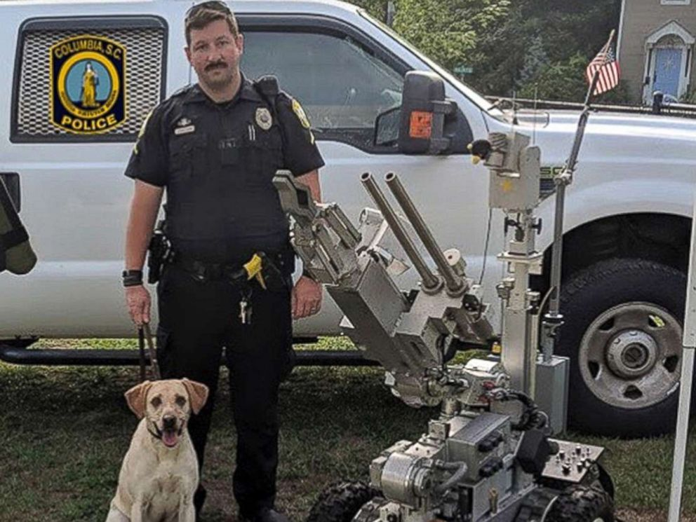 In this undated photo released by the Columbia, S.C., Police Department, Master Police Officer David Hurt is seen with his police dog Turbo.