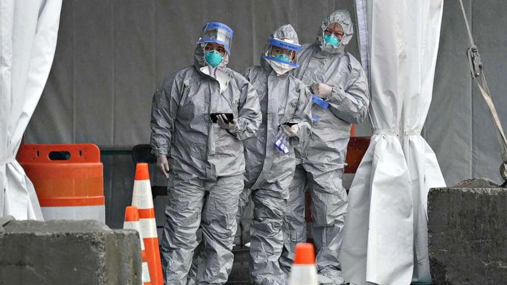 Timothy A. Clary/AFP via Getty Images Workers in protective suits wait for people to arrive by car as Governor Andrew Cuomo opens the State's First Drive Through COVID-19 Mobile Testing Center at Glen Island Park