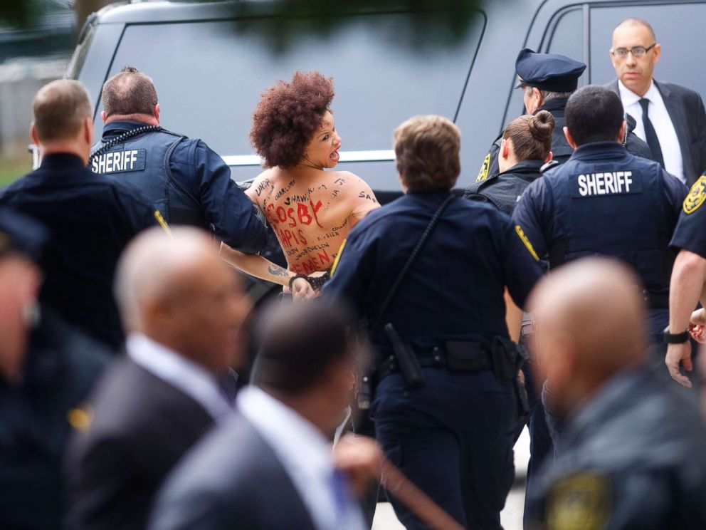 PHOTO: A topless protester wearing body paint is arrested as Bill Cosby arrives at the Montgomery County Courthouse for the first day of his sexual assault retrial on April 9, 2018 in Norristown, Pa.