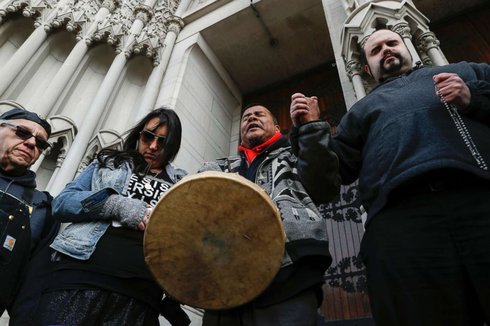 PHOTO: Native American demonstrators hold hands with parishioner Nathanial Hall, right, during a group prayer outside the Catholic Diocese of Covington, Jan. 22, 2019, in Covington, Ky.