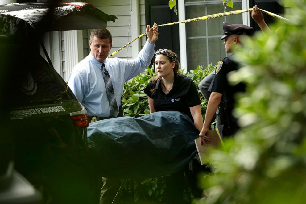 PHOTO: A woman from the Massachusetts Chief Medical Examiners Office, center, uses a gurney to place human remains into a vehicle at a home where two adults and three children were found dead with gunshot wounds, Oct. 7, 2019, in Abington, Mass.